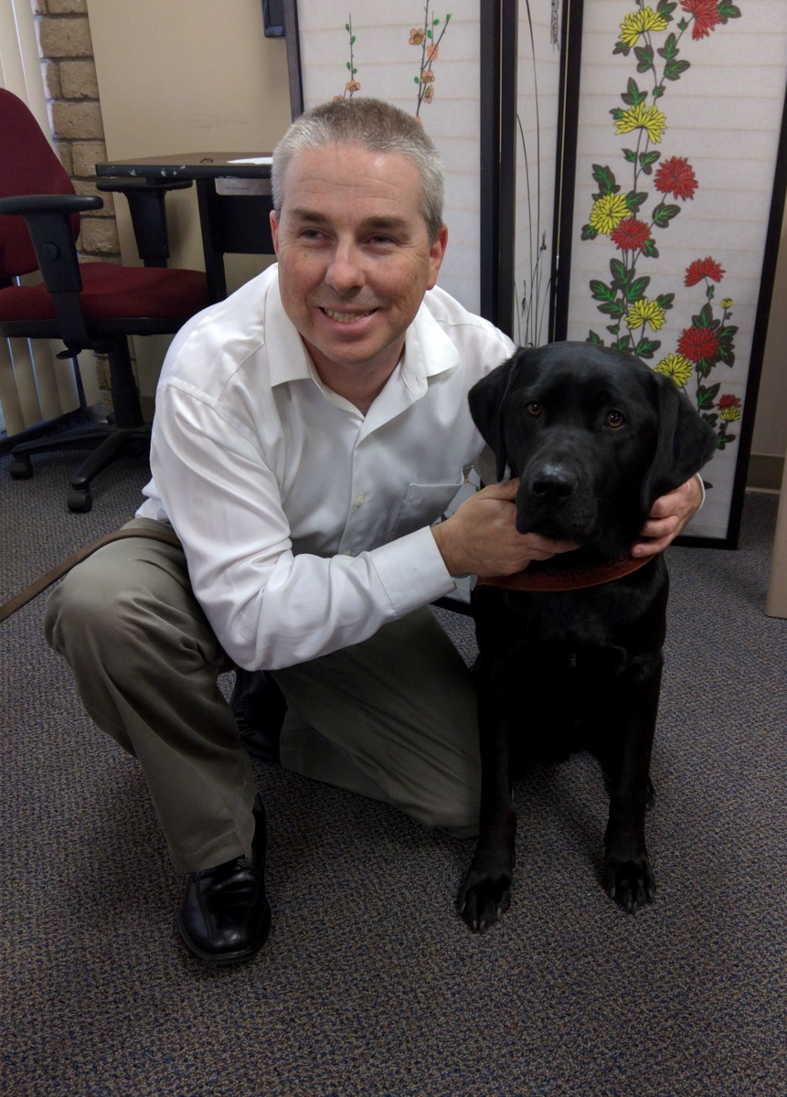 DMC staff Paul at ground level posing with his guide dog