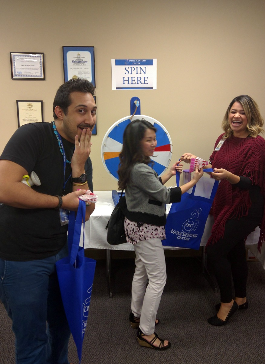 Guests with silly expression at prize wheel, staffed by Grace
