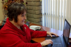 DMC Director Margeson at her desk using laptop