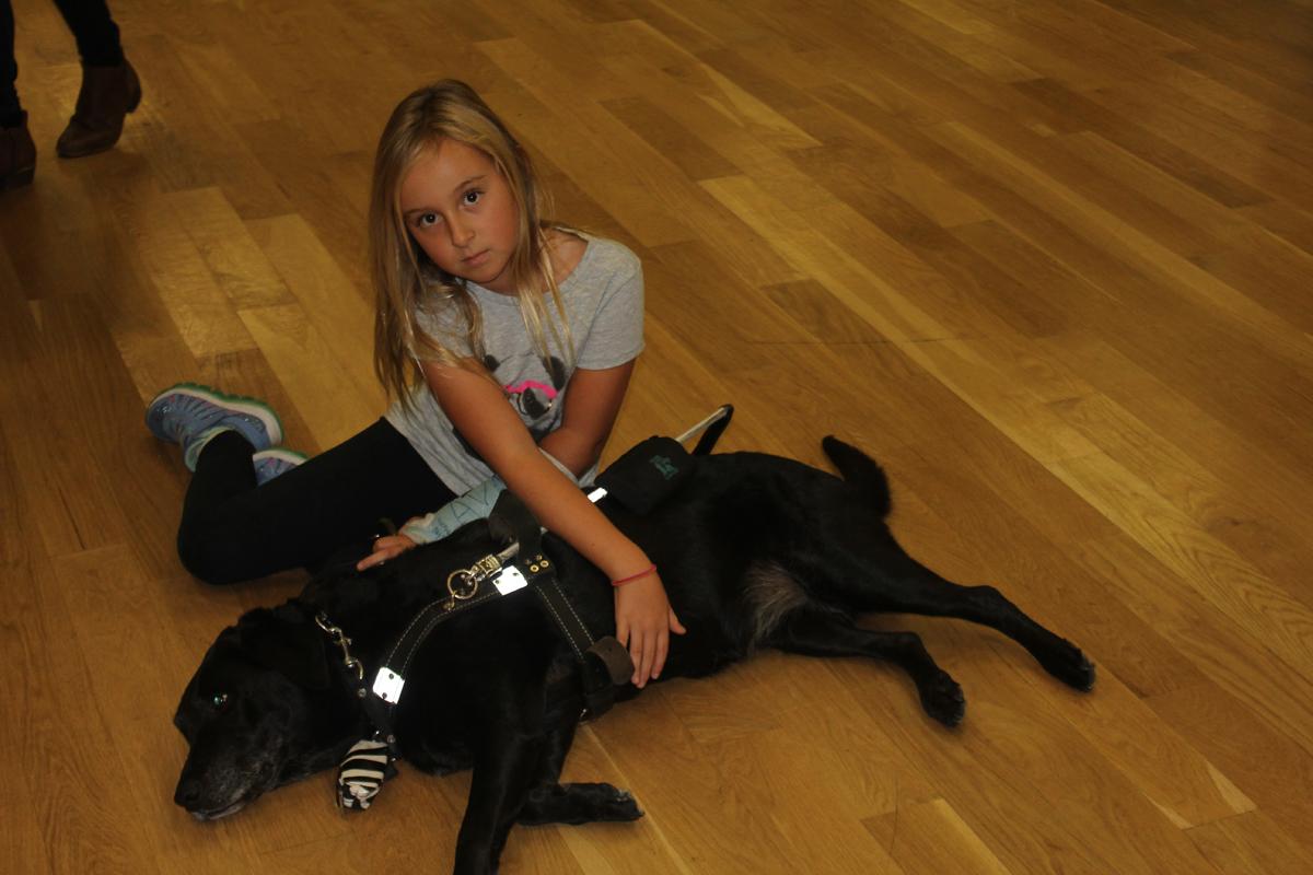 Young girl petting guide dog Ninya both on wood floor