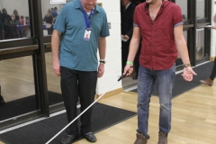 DMC Staff helping Chuy walk with cane while blind folded during sensativity excercise