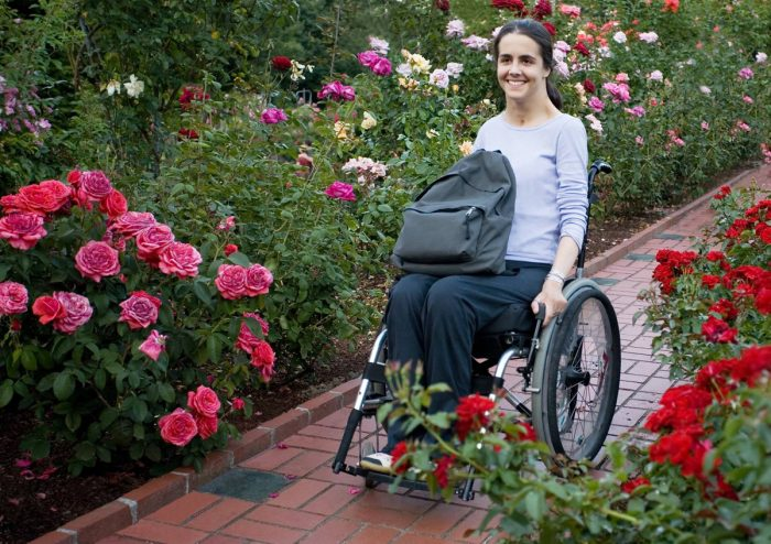 Services Picture of woman in wheelchair with tote on her lap rolling on pavers through a rose garden.