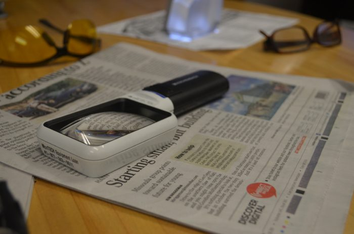 Services AVL picture of magnifying glass on top of newspaper. Skills Training