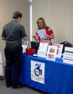 Community Services Outreach picture of staff member and participant at DMC resource table.