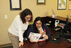Information and Referral Coordinator reviewing resource book with consumer