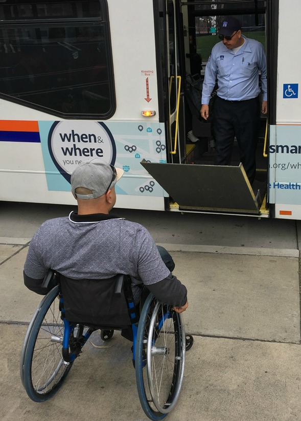 MMP Picture of OCTA bus driver lowering ramp for a man in wheelchair.