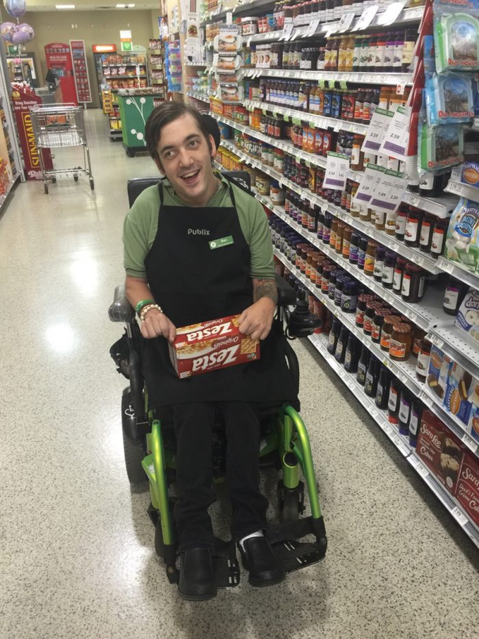 Man in wheelchair stocking shelves at grocery store Employment Assistance