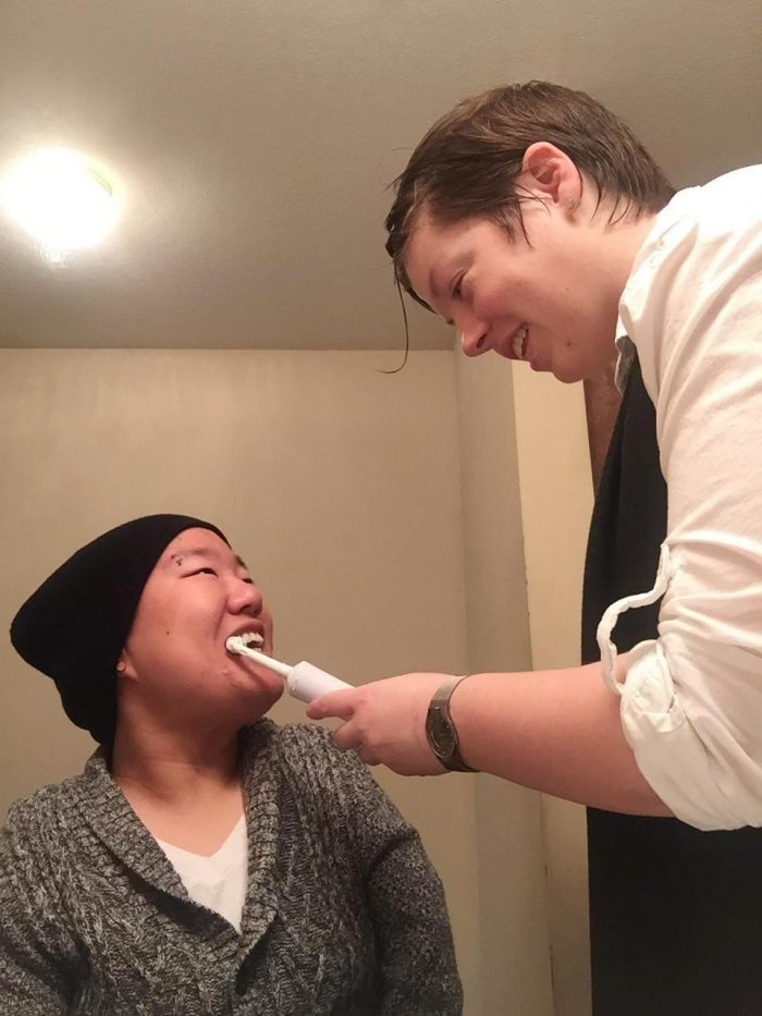 PAS Attendent helping a young adult female brush her teeth.
