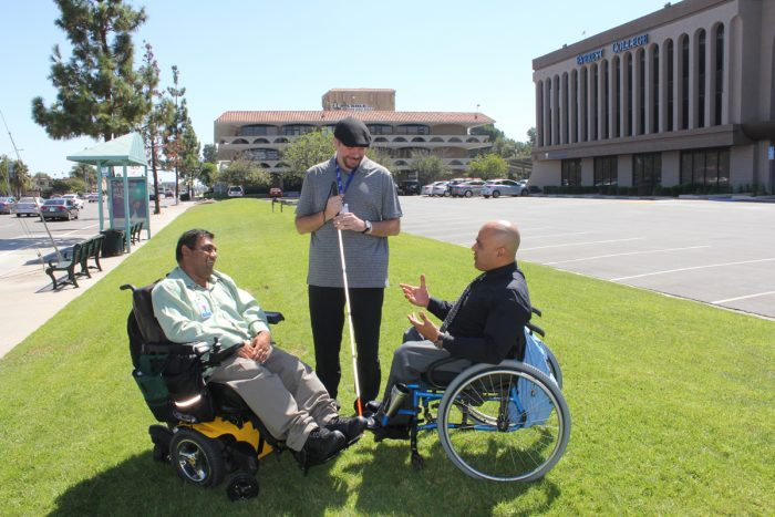 Peer support 3 men with disabilities talking on grass