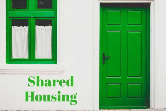 Picture of house with green door and window frame with Shared Housing in text box