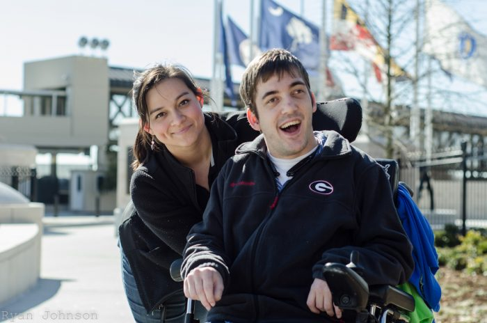 Young adult in power chair with attendent with nursing home in background . people with disabilities