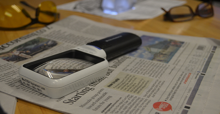 Services AVL picture of magnifying glass on top of newspaper.