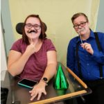 Picture of two youth with photo booth props holding mustaches on their face.