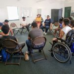 A group of youth with disabilities sitting in a circle having a group discussion.