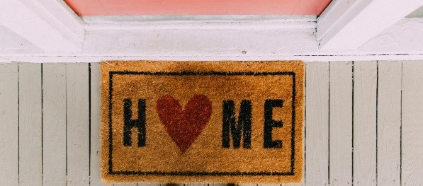"Photo of a tan front door mat with ""home"" in black with a red heart in place of the ""o"""