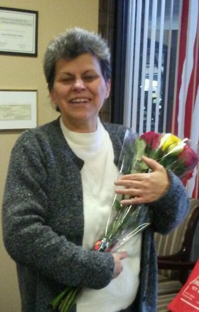 Picture of Maria at DMC offices holding flowers and smiling.
